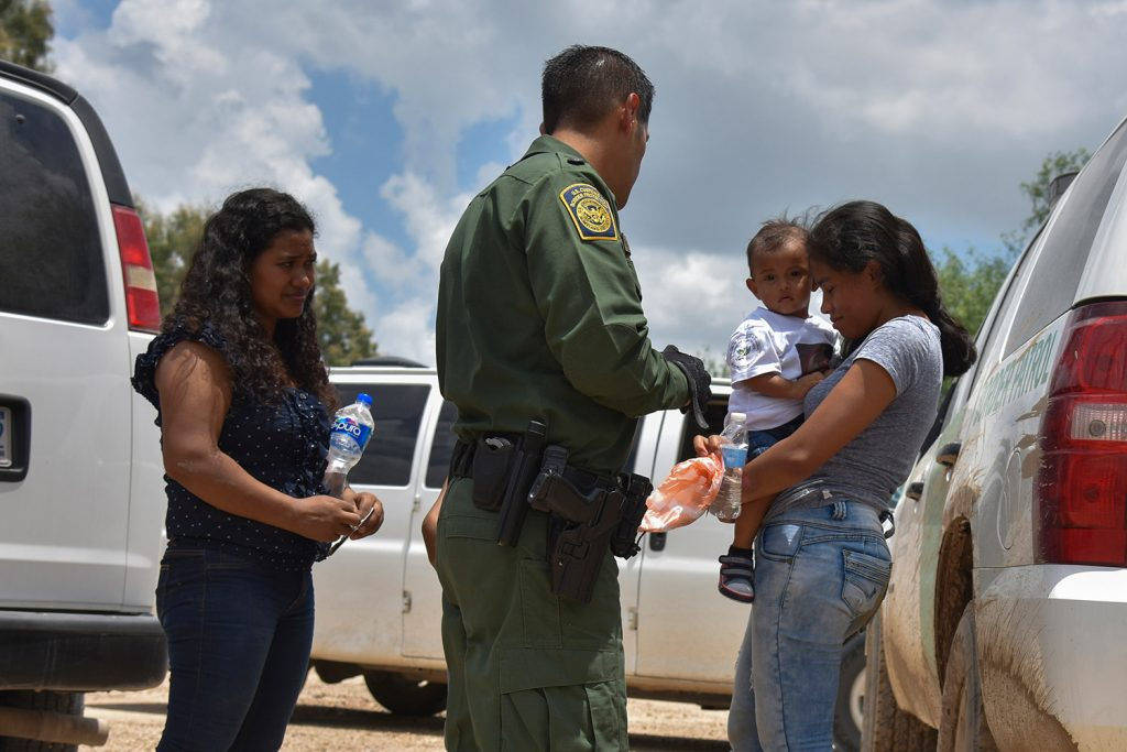 Two young mothers from Honduras and their children are detained by Border Patrol after rafting across the Rio Grande in Granjeno, Texas, in June.