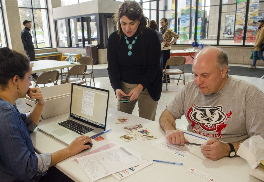 Adriana Ortiz-Burnham, left, and Christine Pittsley talk to Jim Melcher about the World War I postcard he brought in Saturday at the Cultural Building in Augusta. Pittsley works for the Connecticut State Library and was helping the run a digitization event with Maine state workers.