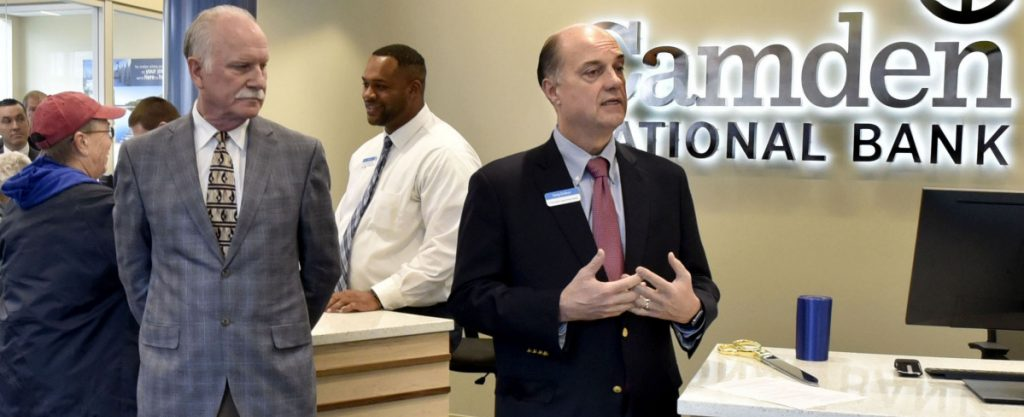As customer Donna Goggin is assisted by teller Alex Green, Camden National Bank President and CEO Greg Dufour, right, and Chairman of the Board Larry Sterrs speak during a grand opening of the bank in the Bill & Joan Alfond Main Street Commons building in Waterville on Monday.