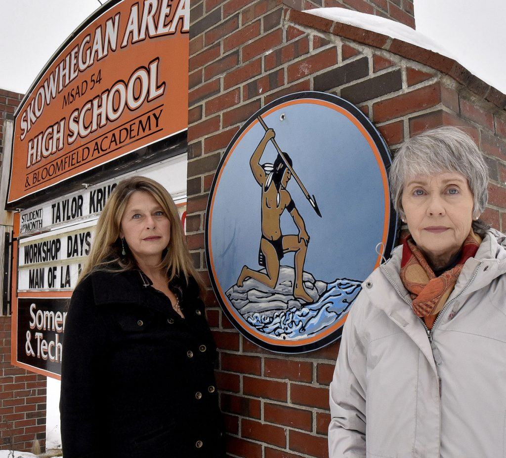 Hope Savage, left, and her sister, Lisa, stand beside the sign at the entrance to the Skowhegan Area High School that displays an image of a Native American on Monday. The Savages and others are urging the school board to cease using Indian as the school mascot.
