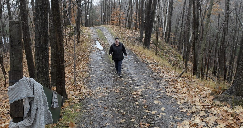 Monique Poulin walks to her home on Nov. 13, down the road that abuts Boothby Street, from the pits located at the Augusta Public Works facility.