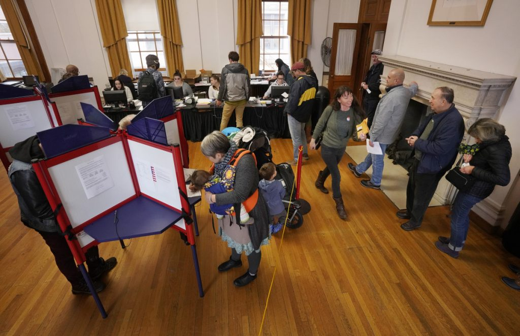 Early voters crowd the booths at Portland City Hall at lunch hour Thursday, the last day Maine residents could pick up absentee ballots. Absentee ballots must be turned in to municipal clerks by 8 p.m. on Election Day, next Tuesday.