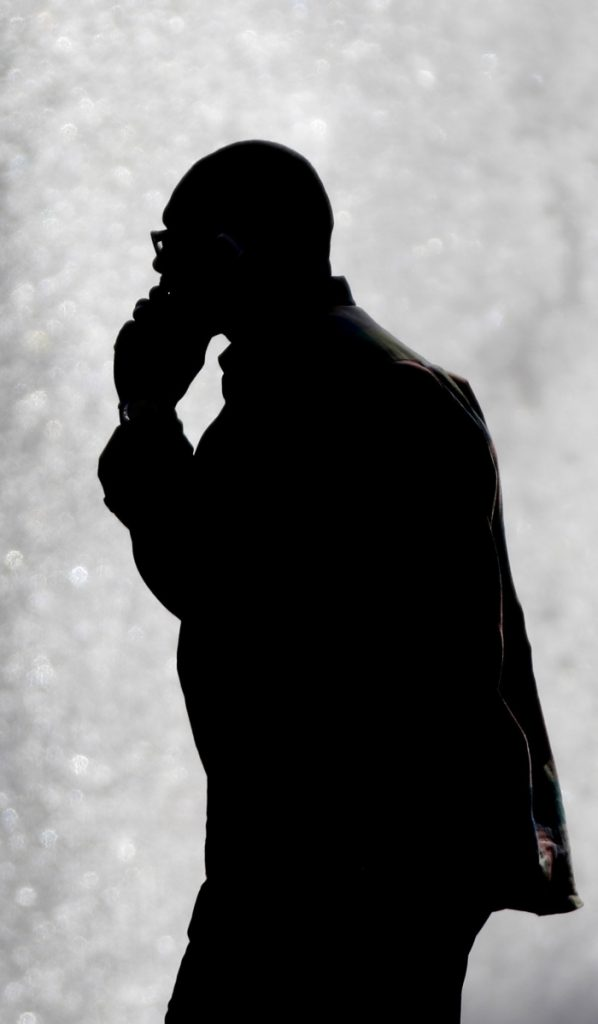 A pedestrian talking on a cellphone is silhouetted in front of a fountain in Philadelphia in 2012.