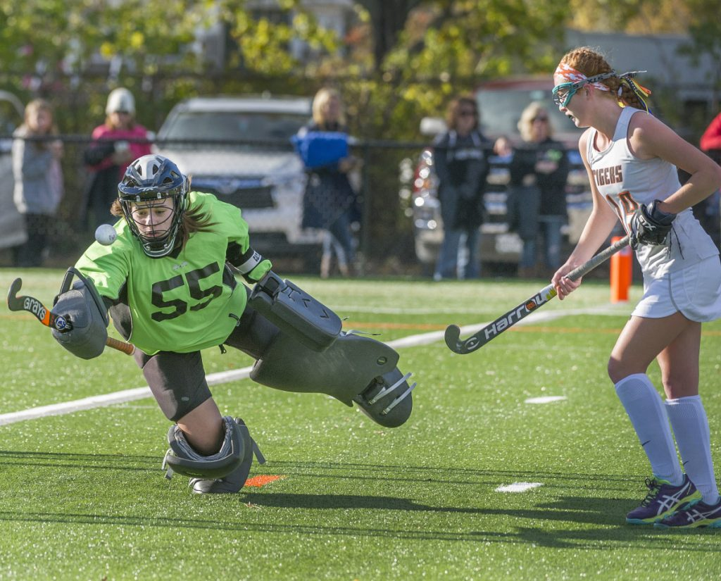 Biddeford goalie Taylor Wildes makes a stick save on a Falmouth shot. Defender Harmonie Coolbroth looks to help on the play. (Staff photo by John Ewing/Staff Photographer)
