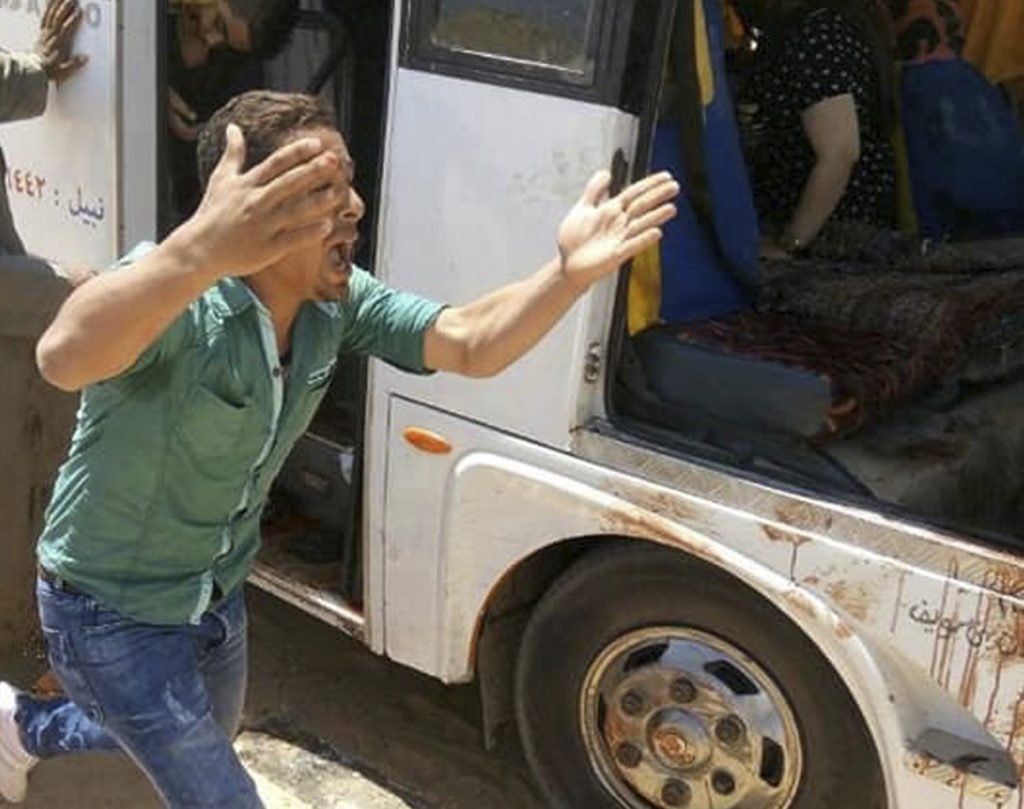 A man screams beside a bus carrying Coptic Christian pilgrims that came under attack by Islamic militants outside Cairo on Friday, killing at least seven and wounding 19 more.