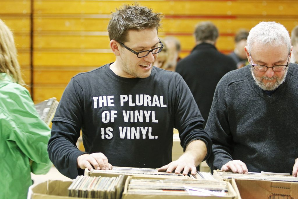 Hundreds of vinyl enthusiasts, including Brian Lozo of Biddeford and Jonathan Gilbert of Portland seek out hidden gems Saturday at the WMPG Record Sale at the University of Southern Maine's Sullivan gym.