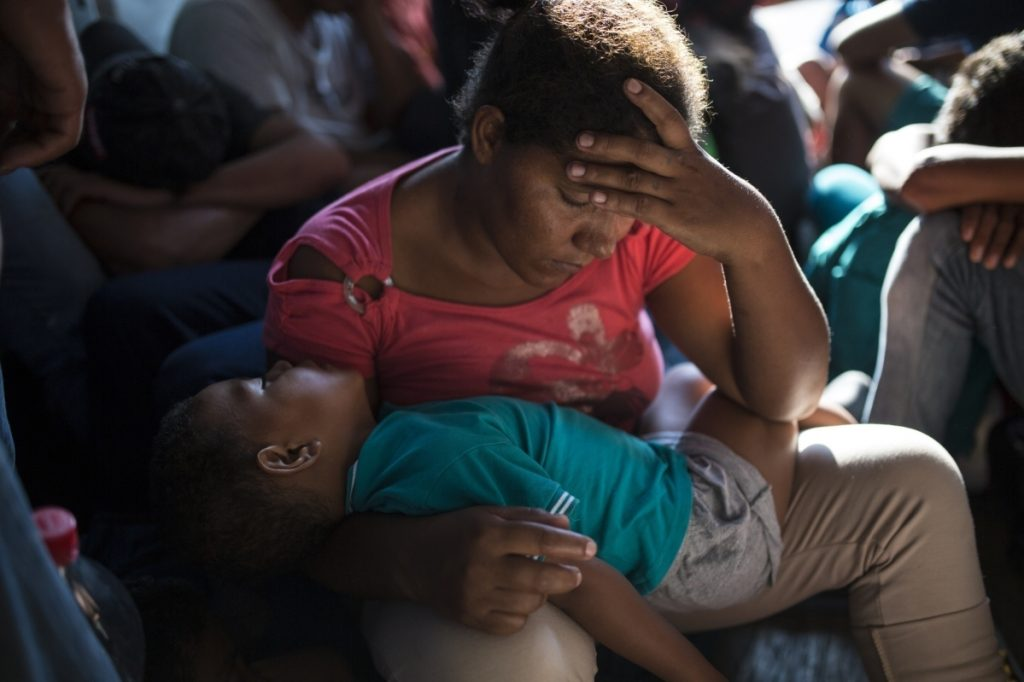 Yamilet Hernandez rests with her son inside a truck between Pijijiapan and Arriaga, Mexico, on Oct. 26. More than 6,000 migrants are traveling through Mexico.