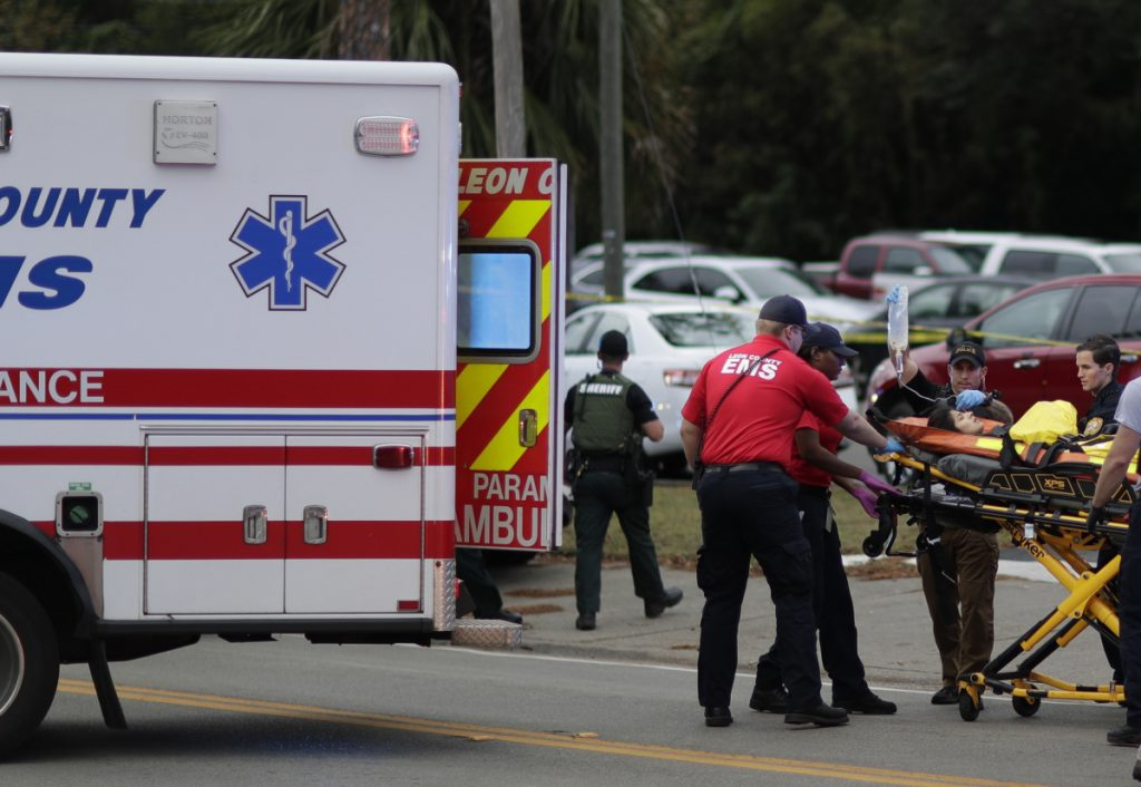 A person is transported from the scene of a shooting Friday in Tallahassee, Fla. A gunman killed two people and critically wounded four others at a yoga studio.