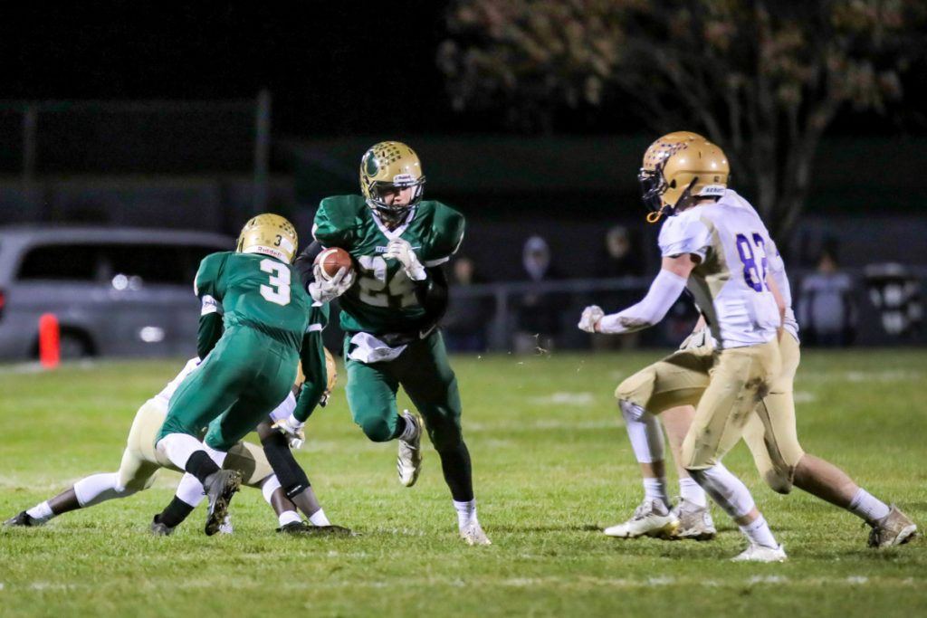 Janek Luksza of Oxford Hills tries to get past Sean Tompkins of Cheverus during their Class A North semifinal Saturday night. Oxford Hills won, 35-6.