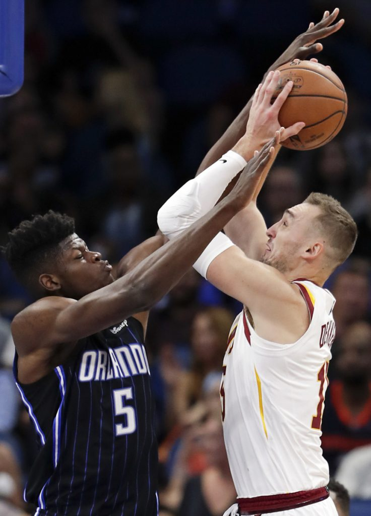Orlando's Mohamed Bamba, left, fouls Cleveland's Sam Dekker during their game Monday night in Orlando, Fla. Evan Fournier hit a jumper at the buzzer and the Magic won 102-100.