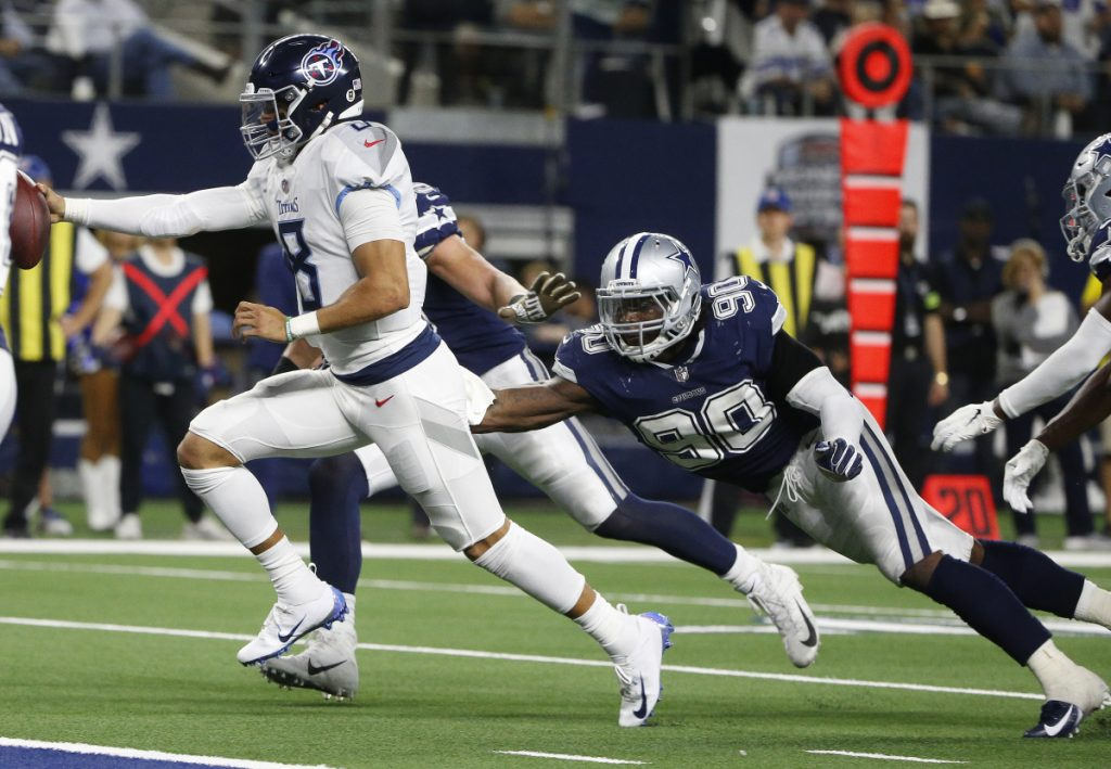 Titans quarterback Marcus Mariota runs for a touchdown against Cowboys defensive end Demarcus Lawrence during the second half of the Titans' 28-14 win on Monday in Arlington, Texas.