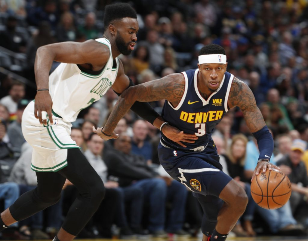 Nuggets forward Torrey Craig, right, drives to the basket past Celtics guard Jaylen Brown in the first half of the Nuggets' 115-107 win Monday in Denver.
