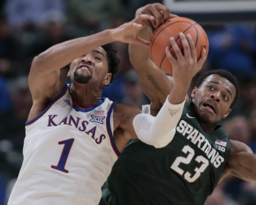 Kansas forward Dedric Lawson, left, battles with Michigan State forward Xavier Tillman during Tuesday's game in Indianapolis.