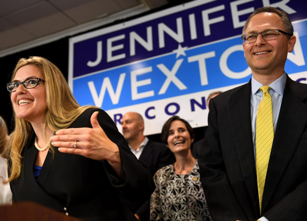 Democrat Jennifer Wexton talks to supporters flanked by her husband, Andrew, Tuesday in Dulles, Va. Wexton beat incumbent Barbara Comstock in Virginia's 10th Congressional District.