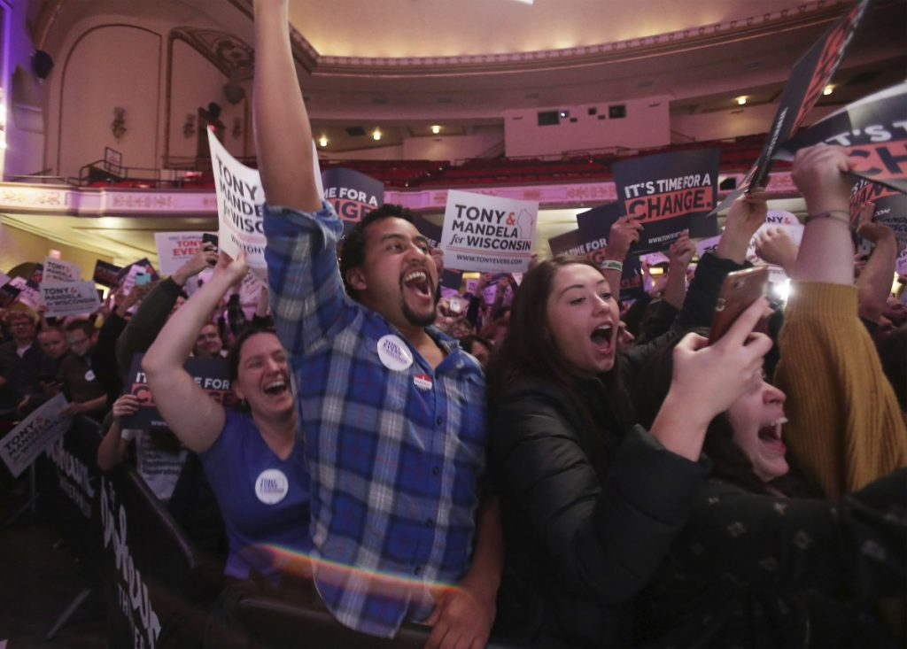 Supporters of Wisconsin Democratic gubernatorial candidate Tony Evers celebrate has he takes the stage during a post-election party at the Orpheum Theater in Madison, Wis., early Wednesday morning.