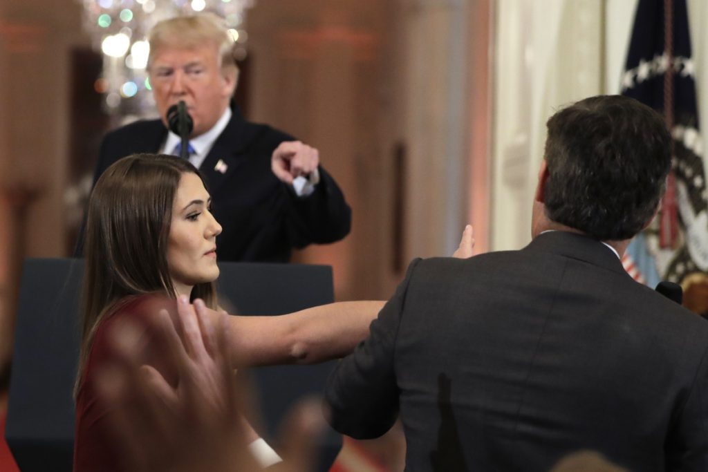 As President Trump points to CNN's Jim Acosta, a White House aide strips Acosta of the microphone while he questions the president during a news conference at the White House on Wednesday.