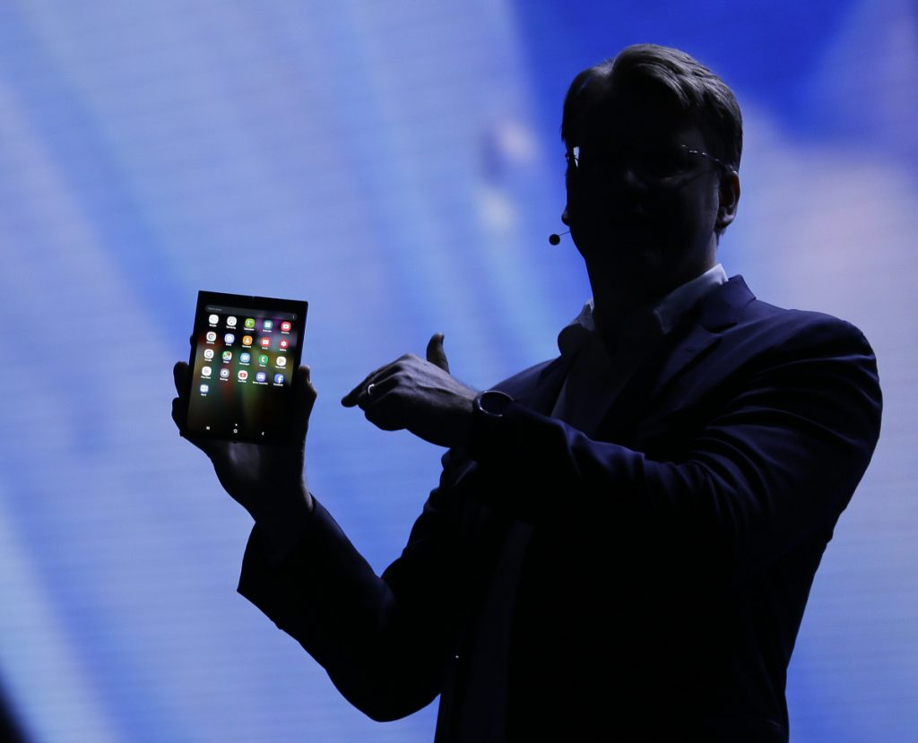 Justin Denison of Samsung shows off a folding smartphone during a developer conference Wednesday in San Francisco. Samsung says it will bring a smartphone with a bendable screen to market next year.