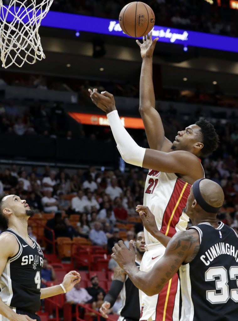 Miami's Hassan Whiteside shoots over San Antonio's Derrick White, left, and Dante Cunningham. Whiteside had 29 points in Miami's 95-88 win Wednesday night.