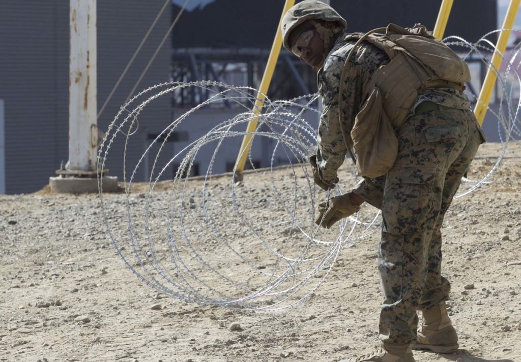 Marine Corps engineers put up razor wire near the San Ysidro Port of Entry where trains pass from the U.S. to Mexico and Mexico to the U.S. on Tuesday.