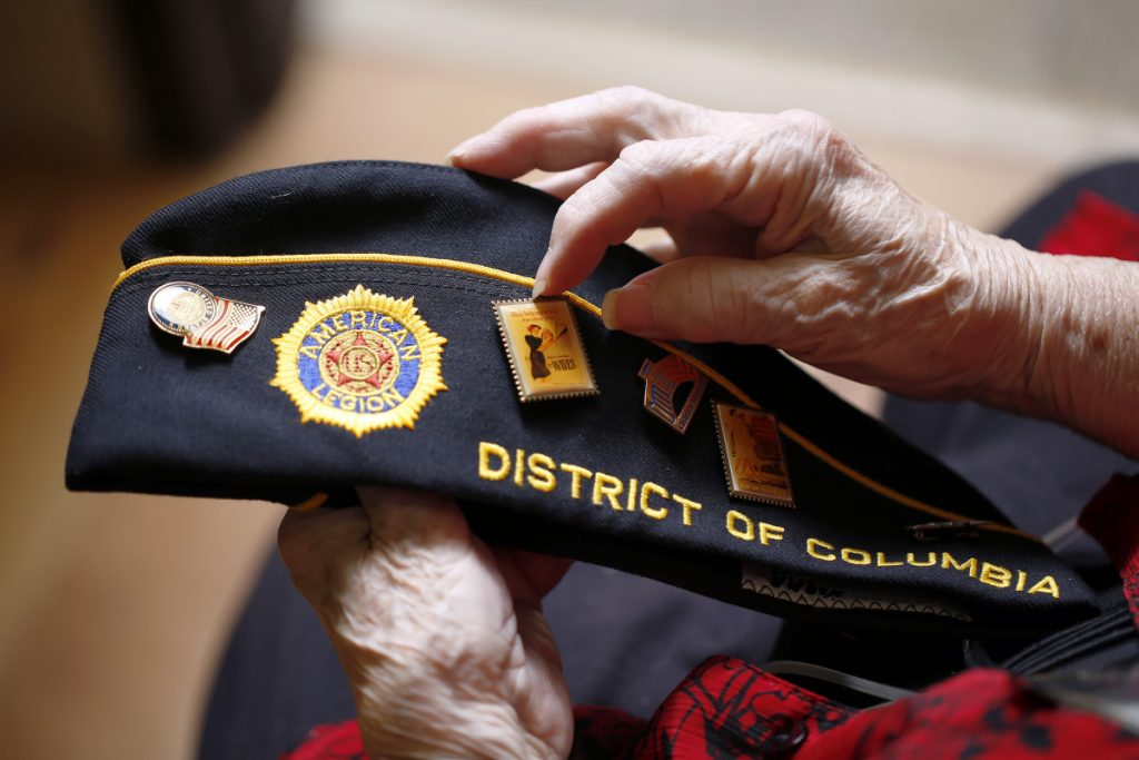 Norma Merrill displays the buttons on her American Legion cap. After retiring, Merrill helped migrant children in Florida and spent countless hours raising money for the Washington D.C. memorial for servicewomen and to support fellow veterans, many of whom were homeless.