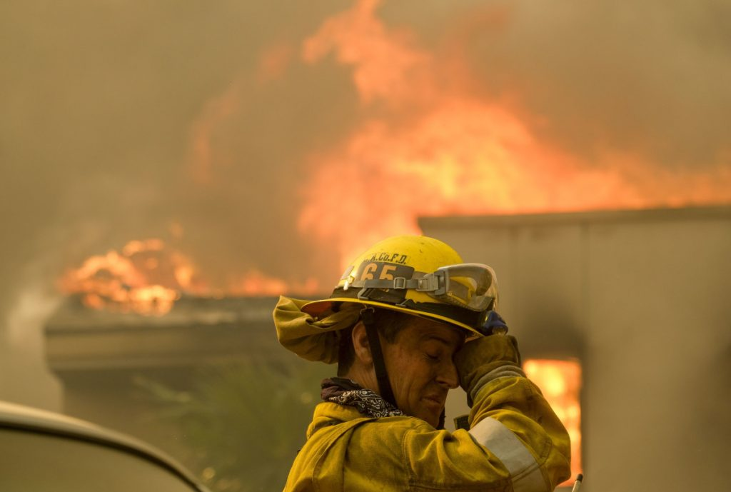 A firefighter battles the heat near a residence in Malibu, Calif., on Friday. The cause of the 140-square-mile blaze is not yet known.