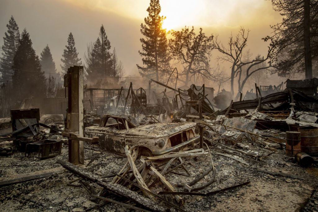 A vintage car rests among debris as a wildfire ravages Paradise, Calif., a town of about 30,000. Several of those killed were found inside burned-out cars. Drivers fleeing Paradise could feel the heat from the blaze as they waited in traffic.