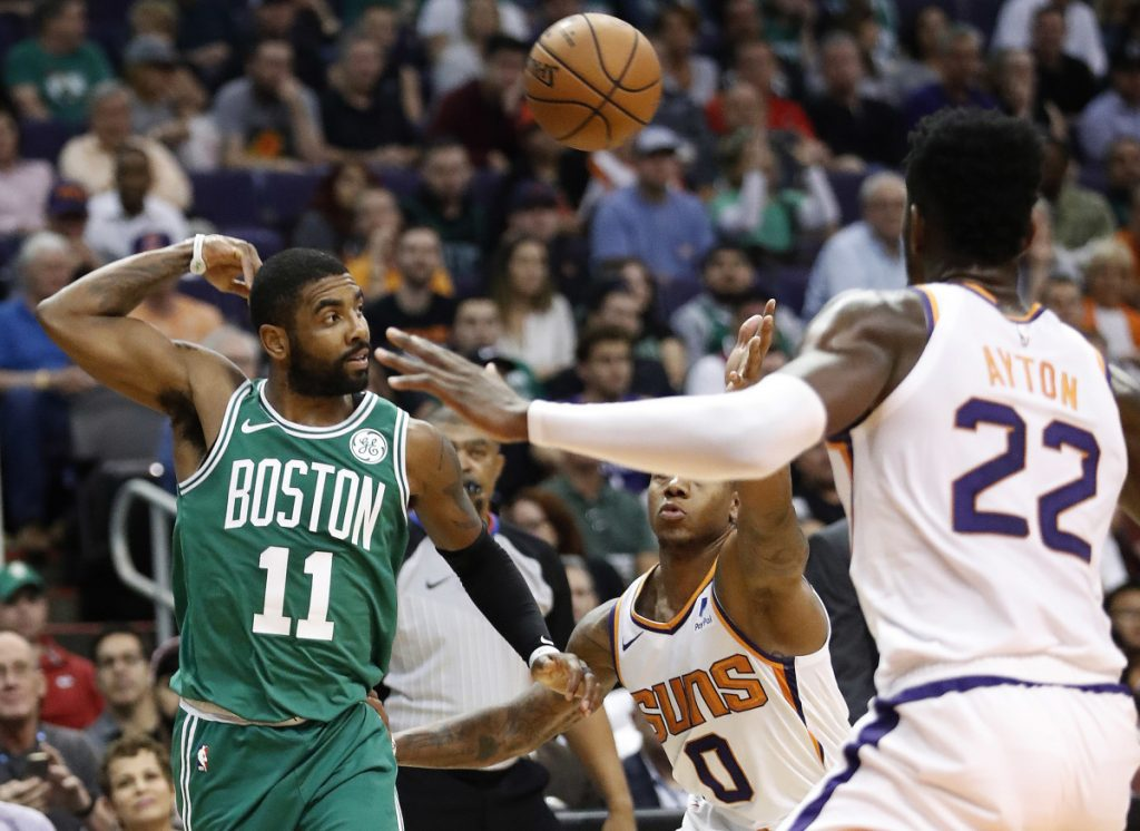 Boston Celtics guard Kyrie Irving (11) throws a pass over Phoenix Suns guard Isaiah Canaan (0) during the first half of an NBA basketball game Thursday, Nov. 8, 2018, in Phoenix.