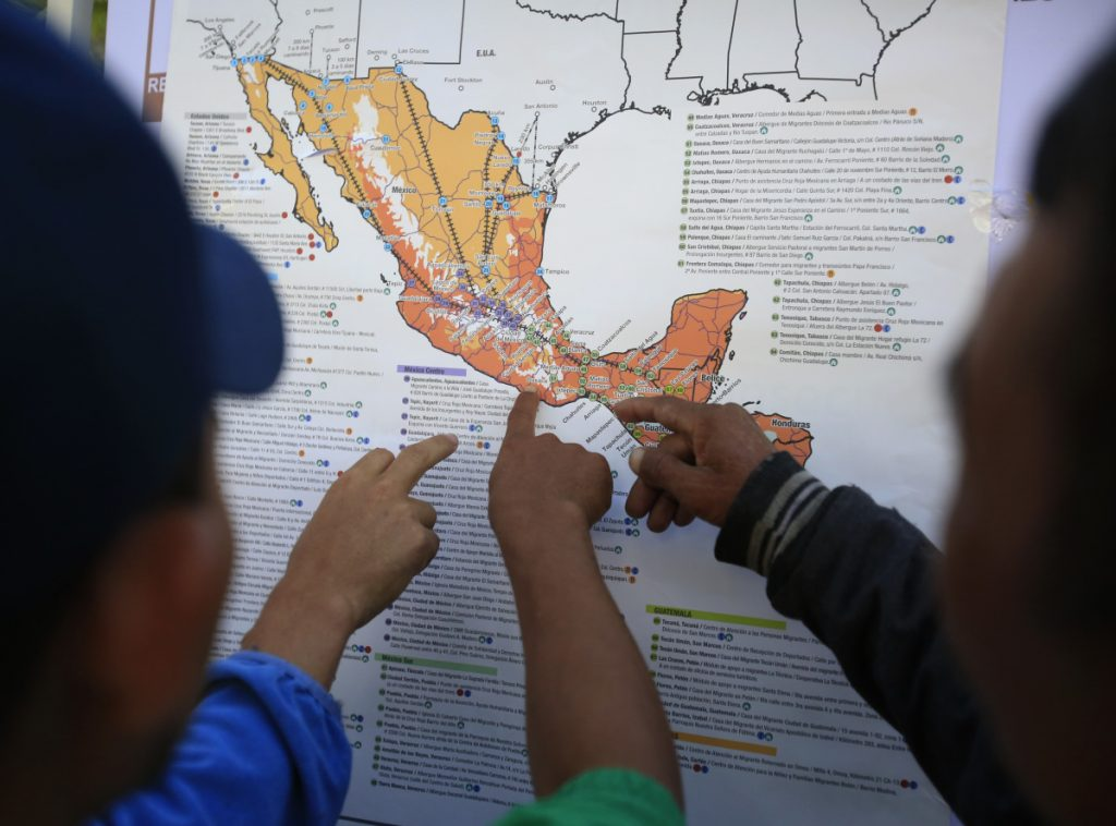 Migrants discuss their journey using a map posted inside the sports complex where thousands have been camped out for several days in Mexico City.
