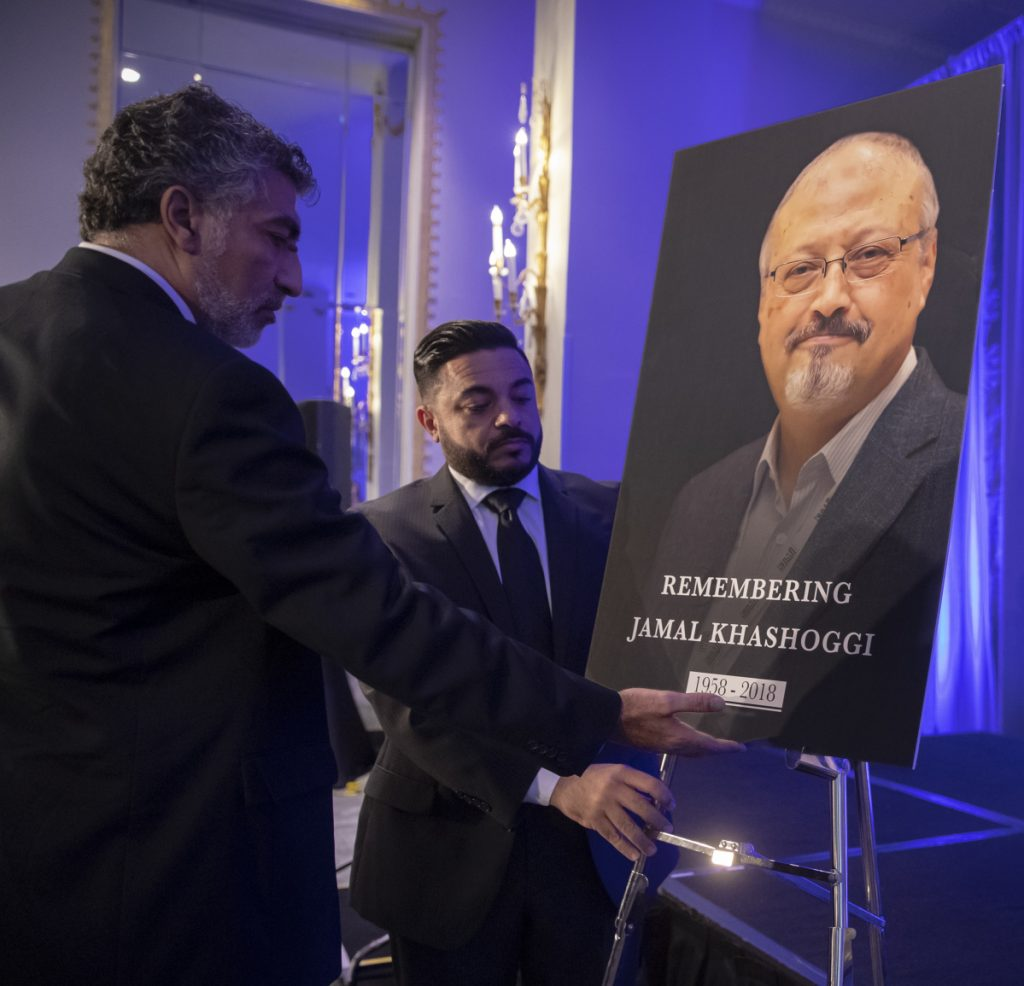 Mongi Dhaouadi, left, and Ahmed Bedier set up an image of slain Saudi journalist Jamal Khashoggi before an event to remember the Washington Post columnist who was killed on Oct. 2.