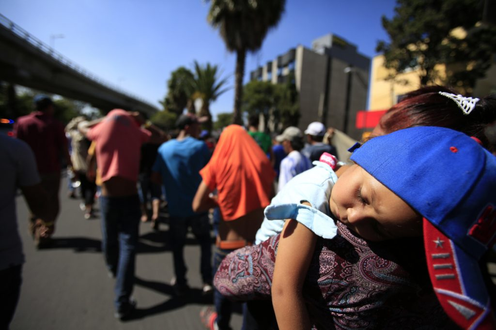 A sleeping Honduran girl is carried as a group of Central American migrants, representing the thousands participating in a caravan trying to reach the U.S. border, walk through Mexico City.