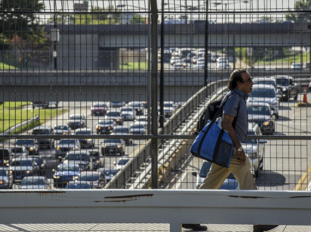 A pedestrian crosses over rush-hour traffic on the Southwest Freeway in Washington in September 2017. America's love affair with the automobile appears to be on the wane.