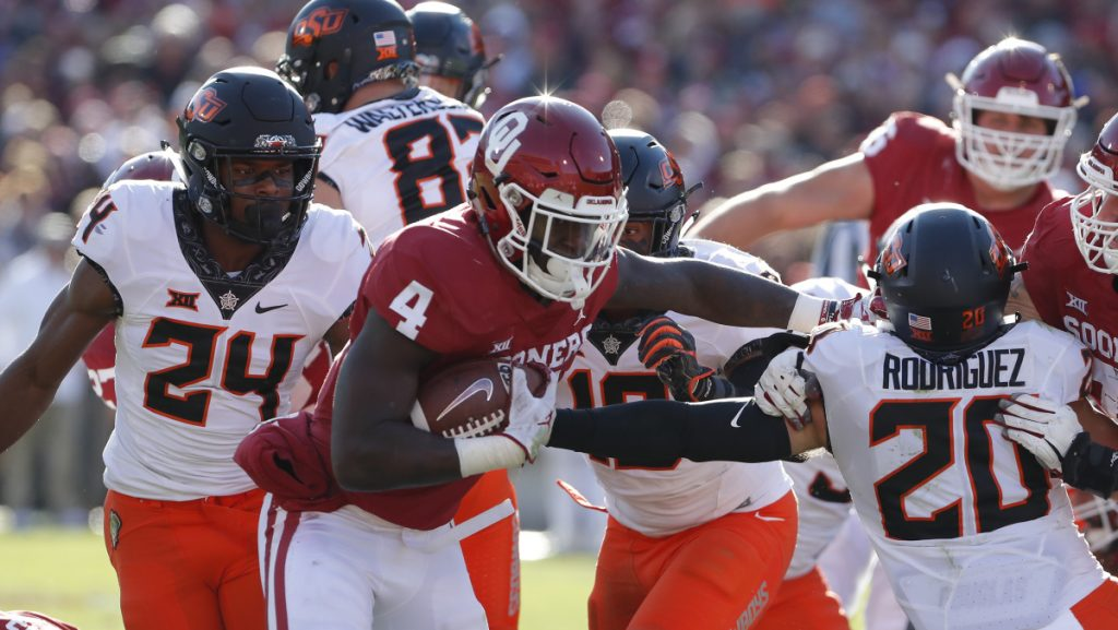 Oklahoma running back Trey Sermon escapes an attempted tackle by Oklahoma State safety Jarrick Bernard, left, and safety Malcolm Rodriguez during the Sooners' 48-47 win Saturday.