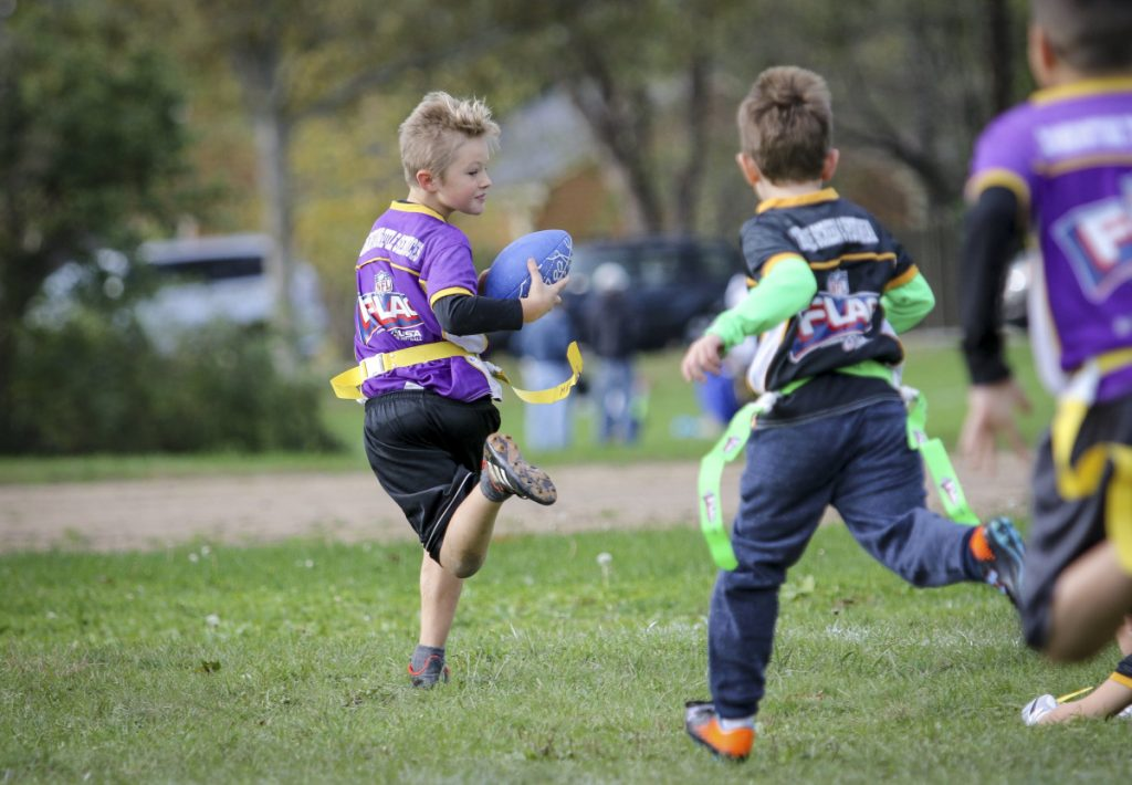 Mateo Pulaski, left, runs for the end zone before realizing he lost a flag during a flag football game in Portland.