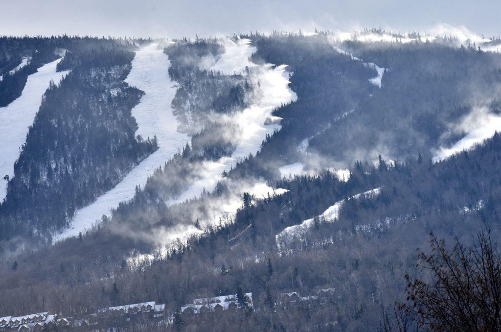 The Sugarloaf ski resort is covered with natural snow as well as man-made snow shot Monday from snow guns at right. The mountain opens Friday.