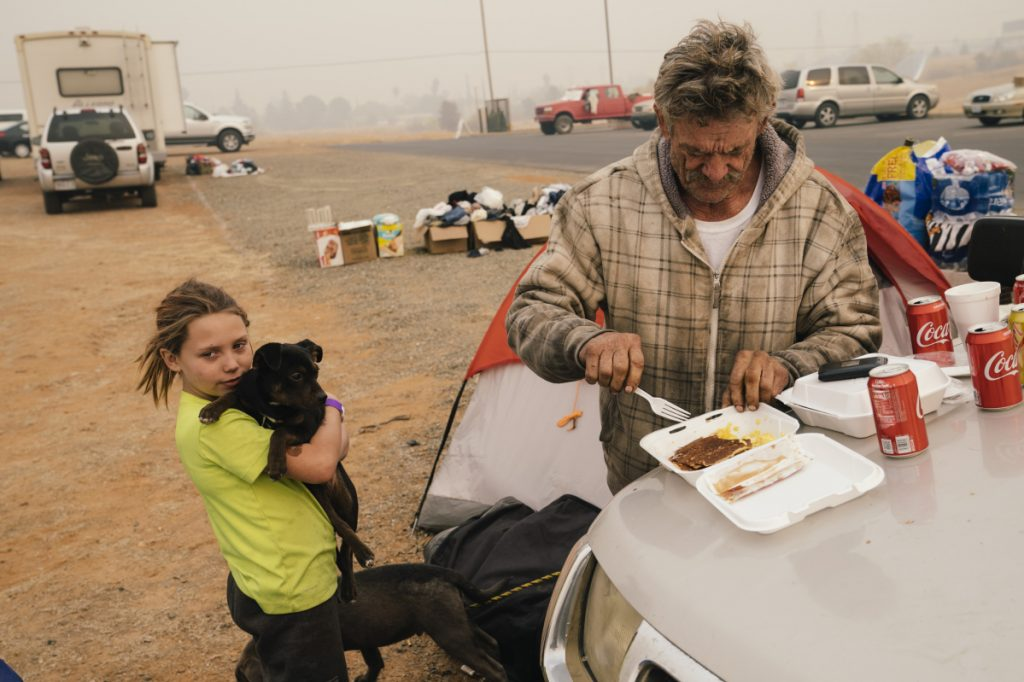 After fleeing the Camp Fire, auto mechanic David Neeley of Berry Creek, Calif., and his 10-year-old daughter, Faith, are holed up at the Red Cross evacuation center at the Church of the Nazarene in Oroville, Calif., on Tuesday.