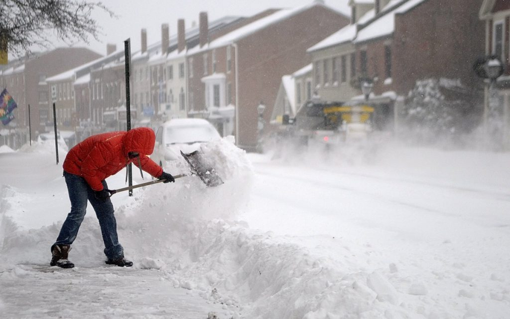 Nathan Sennett shovels snow of the sidewalk in front of his business in Hallowell in 2013.