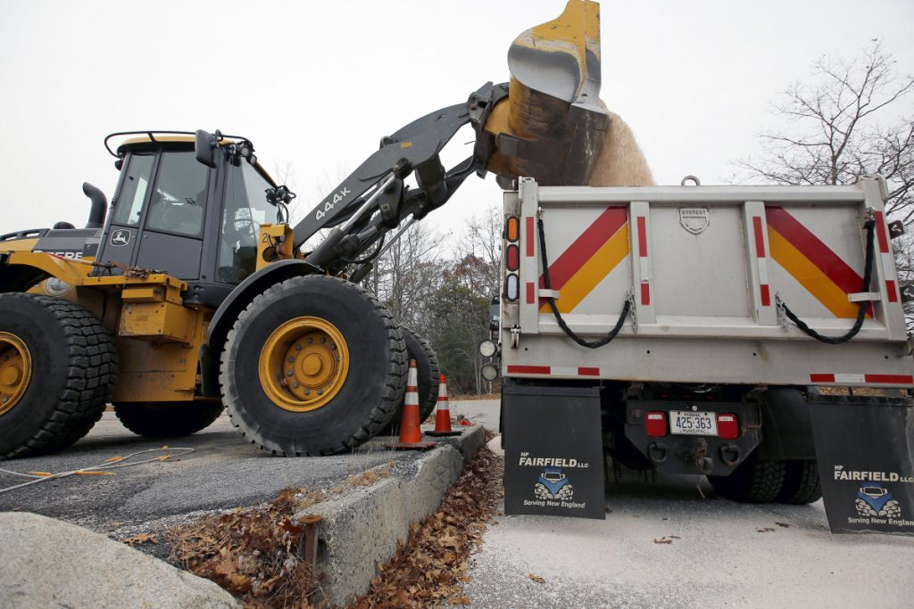 """Adam Enman, a mechanic for the Cape Elizabeth Public Works Department, uses a bucket loader to dump road salt into the last of the town's fleet of trucks Thursday in preparation for a winter storm. """"We load up three trucks and hope we don't use any of them,"""" Enman joked."""