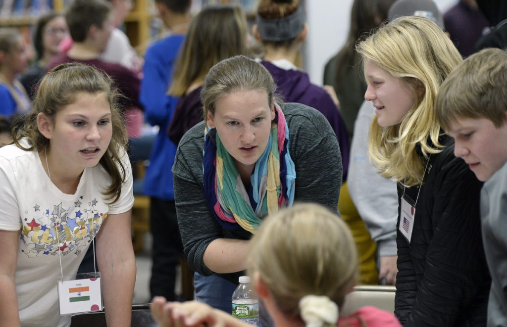 Anna McGinn, center, leads a simulation of the global summit on climate change with seventh-gragers at Loranger Middle School in Old Orchard Beach on Nov. 5. From left are Sarah Davis, McGinn, Lyla Kuchenbecker and Gabe Edwards.