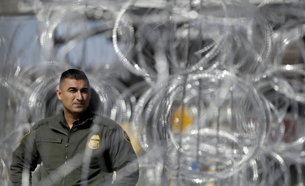A U.S. Border Patrol agent looks through concertina wire during a tour of the San Ysidro port of entry on Friday in San Diego.