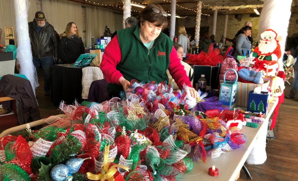 Pauline Day of Albion lays out holiday wreaths she made out of mesh ribbon at a craft fair at the Olde Mill Place in Vassalboro on Saturday.