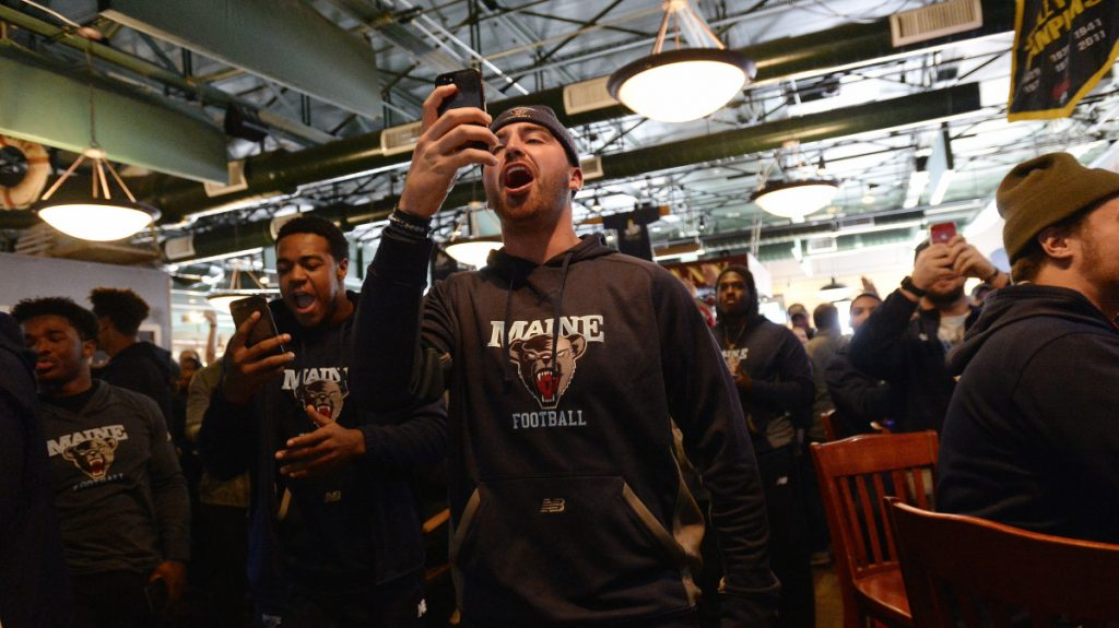 Drew Belcher reacts as the University of Maine football team finds out they get the 7th seed in the FCS playoffs during a watch party at Sea Dog Brewery Company in Bangor on Sunday.