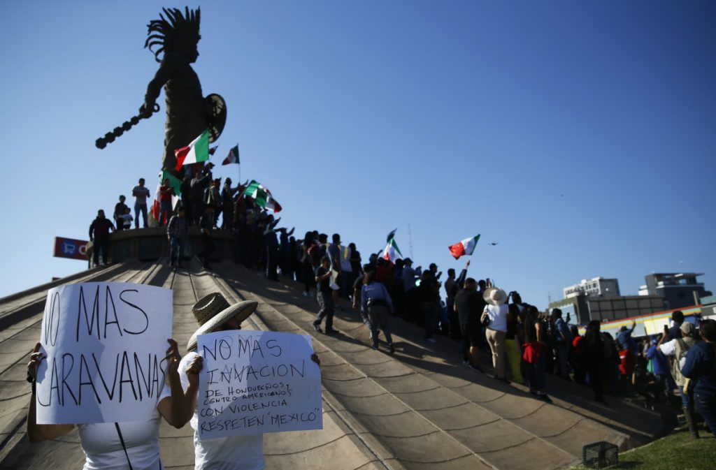 Protesters gather at a statue of Aztec ruler Cuauhtemoc in Tijuana, Mexico, to urge thousands of Central American migrants to return to their countries.