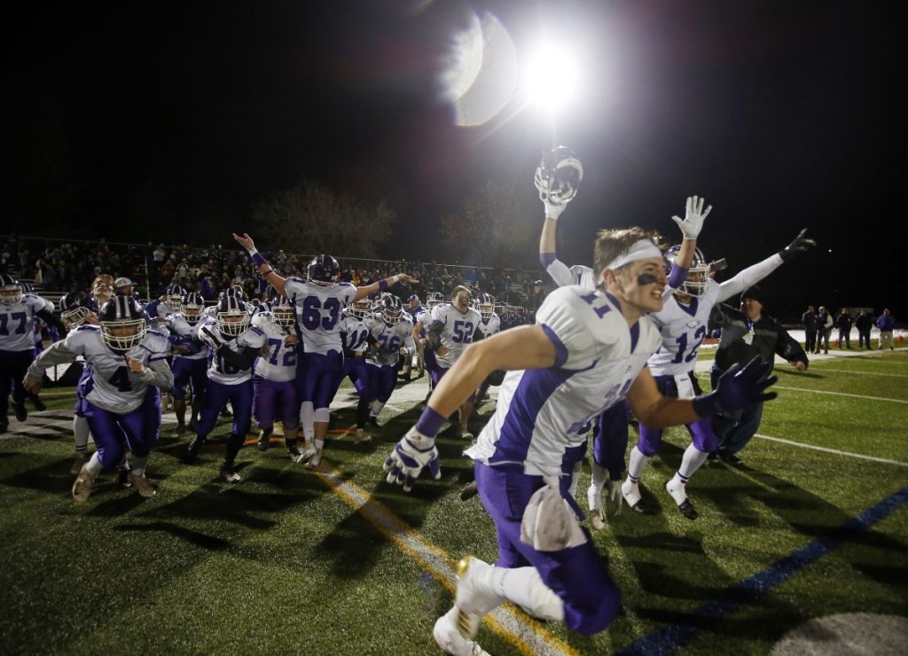 Marshwood players rush onto the field to celebrate their 49-0 victory over Brunswick in the Class B state championship game Saturday night at Fitzpatrick Stadium.