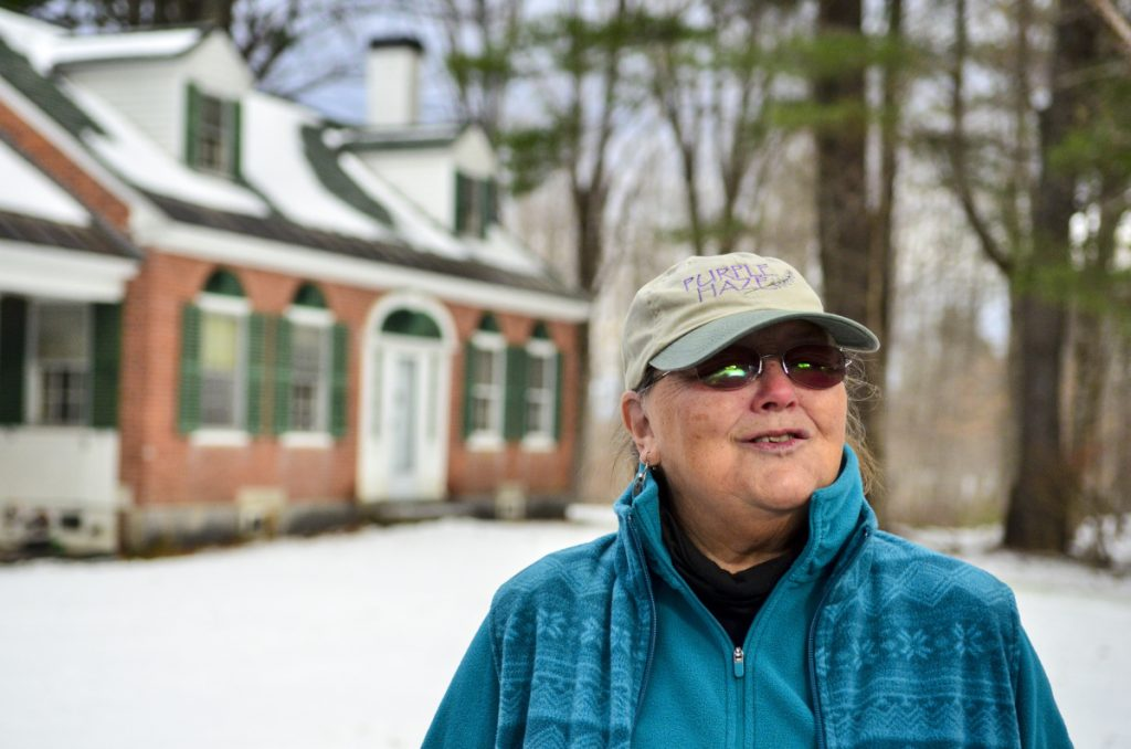 "Dale Potter-Clark, standing near the brick house built in 1825, said, ""We would all love to see that building saved."""