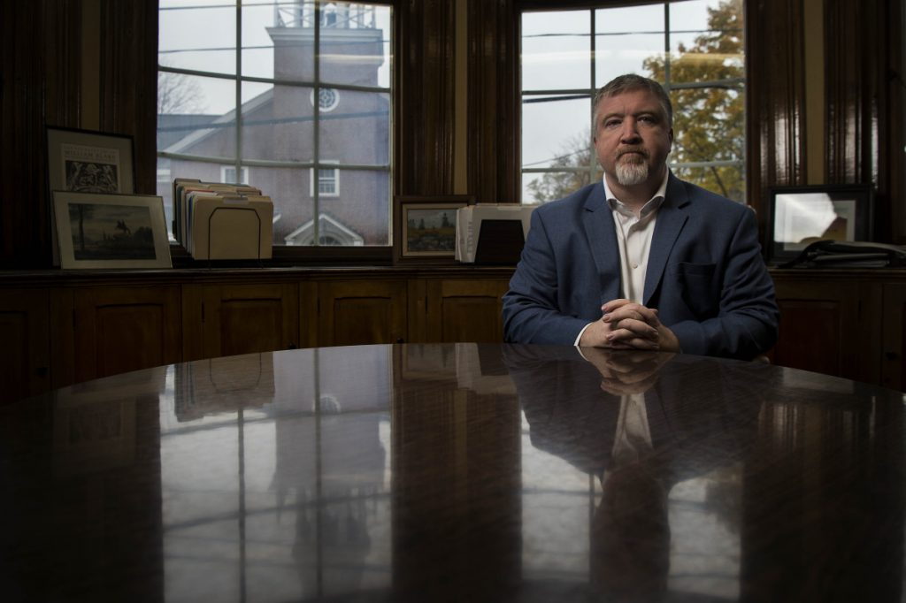 Eric Brown, interim president of the University of Maine at Farmington, sits for a portrait in his office in Farmington on Nov. 2. The University of Maine system is moving ahead with a nationwide search for a permanent president that it expects to culminate in an appointment in June 2019.