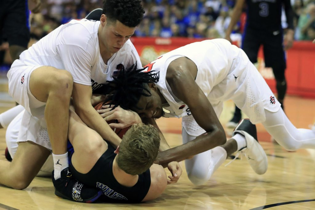 Duke forward Jack White (41) tries to hold on to a rebound as San Diego State guard Jordan Schakel (20) and forward Jalen McDaniels (5) try to wrestle it away during the first half of an NCAA college basketball game at the Maui Invitational, Monday, Nov. 19, 2018, in Lahaina, Hawaii. (AP Photo/Marco Garcia)