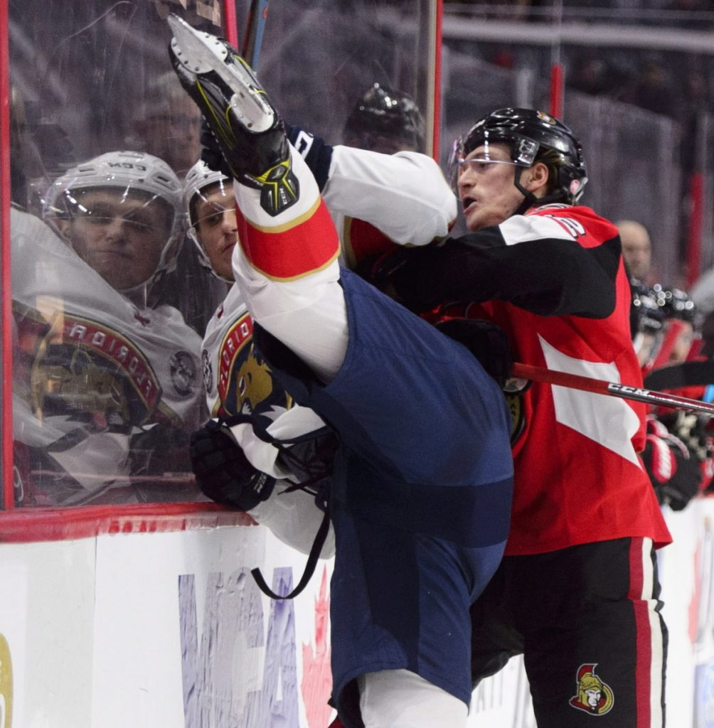 Thomas Chabot of the Ottawa Senators slams Nick Bjugstad of the Florida Panthers into the boards during the first period of Florida's 7-5 victory Monday.