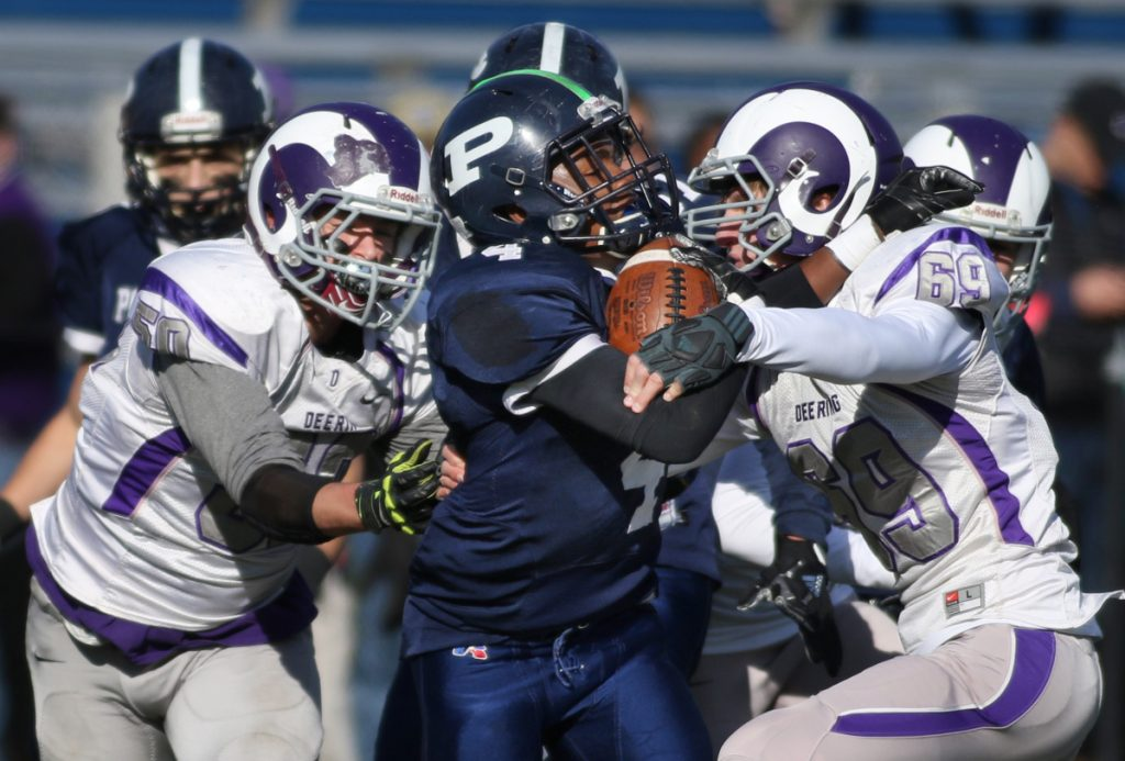 Last year Blaize Vail, left, and Jason Pichette of Deering put the squeeze on Terion Moss and Portland, to win 22-20. This year's game will be played a day early with a frigid holiday forecast.