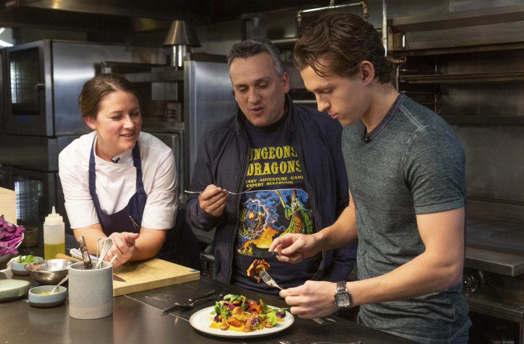 "Chef Jessica Largey watches as ""Avengers"" co-director Joe Russo, center, and ""Spider-Man"" actor Tom Holland try a pumpkin dish she prepared."