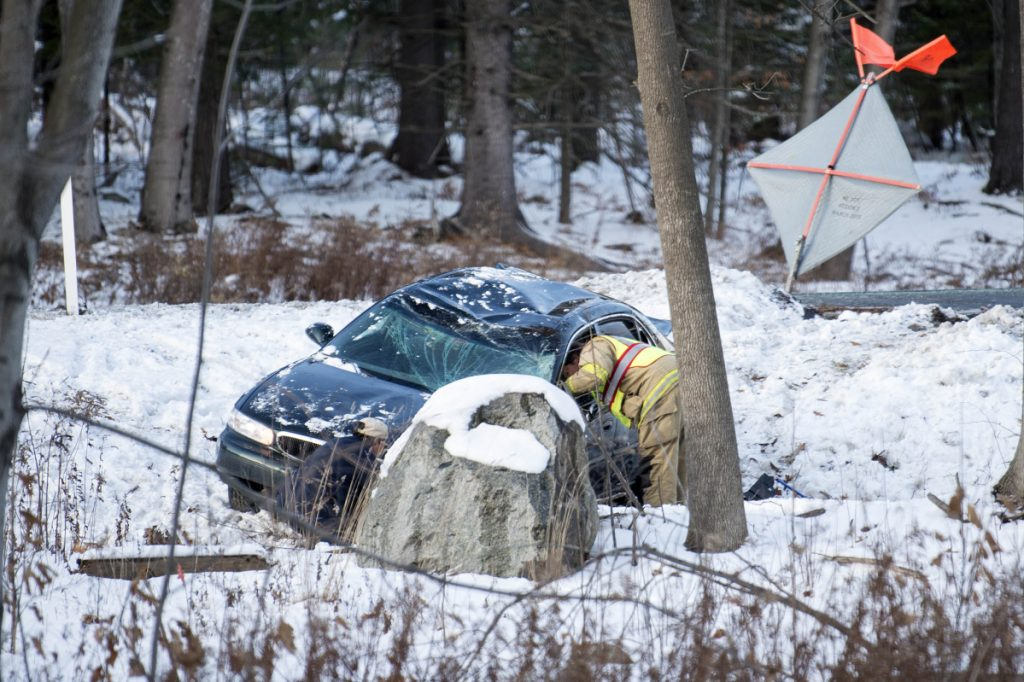 Lt. Scott Holst of the Waterville Fire Department inspects a car that went off the road Wednesday near mile marker 127 on Interstate 95 in Waterville. Staff file photo by Michael G. Seamans